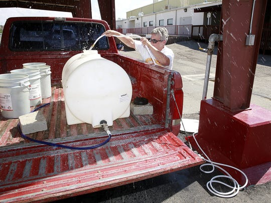 Margo Kaiser, of Crouch Mesa, gets water on June 21 from a filling station at McGee Park in Farmington.