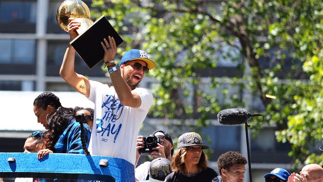 Golden State Warriors guard Stephen Curry (30) holds up the Larry O'Brien Championship Trophy during the championship parade in downtown Oakland.