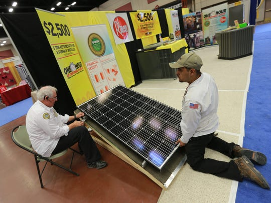 Ron Bacchus, left, and Bryan Jasso prepare a solar panel in the Hour Hour Air Conditioning and Heating/Rheem display area of the spring show in February 2017.