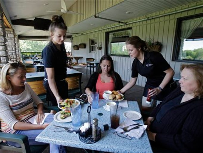 In this June 6, 2014 photo, servers Lindsey Hayden, second from left, and Emma Franz serve lunch to patrons at Coppertop restaurant in Valley City, Ohio. The Fed offered a mixed message on the economy Wednesday: Growth is strengthening, and the unemployment rate is steadily falling. Yet by some measures, it suggested, the job market remains subpar.