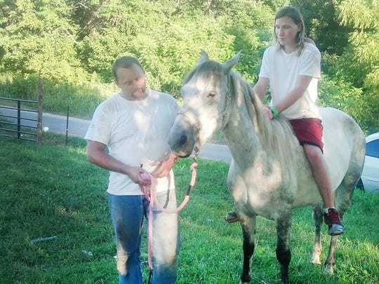 Lisa Swanson's son Frederick Rhines, 18, rides mustang Catalina in Sparta, Tenn. in August while her husband Paul holds the horse. The Swanson family adopted Catalina from Vic White of Portland.