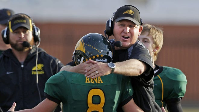 Show Low's Brice Rova is greeted by Head Coach Randy Ricedorff after a he scored a touchdown against Florence during their Division IV semifinal game Saturday Nov. 19, 2011 in Phoenix.