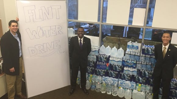 Paul All II, Gregory Joyce II and William Johnson, all members of the Cleveland State University student government, stand in front of their donation drive for residents of Flint, Michigan. (Photo courtesy of William Johnson)