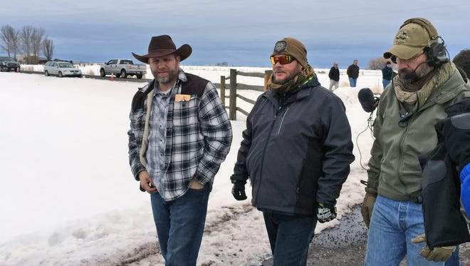 Ammon Bundy, left, approaches an FBI gate at the Burns Municipal Airport in Oregon on Friday, Jan. 22, 2016.