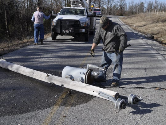 A utility employee prepares to remove a broken transformer from a power pole after an Oklahoma man slammed into the pole Saturday afternoon, breaking it in half. The accident knocked out power in the area along Baxter County Road 69.