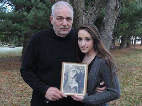 Gaetano Acerra, 58, and his daughter, Alexis Acerra, 19, hold a photo of Gaetano Acerra's parents, Mary Acerra, 86, and Ferdinando Acerra, 89, who died within hours of each other following their 65th anniversary.