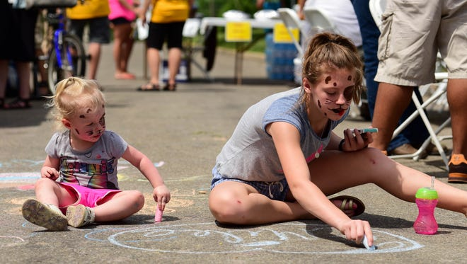 Madisen Padgett ,12, a Woodside eighth-grader, and her little sister, Emilee, 2, work on sidewalk art on Saturday, June 11, 2016, during the Capitol Park Neighborhood Association's renovation and revitalization block party.