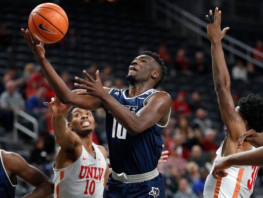 Rice's Robert Martin, center, shoots over UNLV's Shakur Juiston, left, during the first half of an NCAA college basketball game Monday, Nov. 20, 2017, in Las Vegas. (AP Photo/John Locher)