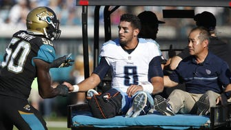 Jaguars outside linebacker Telvin Smith (50) speaks to Marcus Mariota (8) after the Titans quarterback injured his leg during the third quarter Dec. 24 at EverBank Field in Jacksonville, Fla.