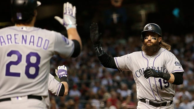 Colorado Rockies' Charlie Blackmon (19) celebrates with Nolan Arenado (28) after hitting a solo home run against the Arizona Diamondbacks during the sixth inning of a baseball game Saturday, March 31, 2018, in Phoenix. (AP Photo/Matt York)