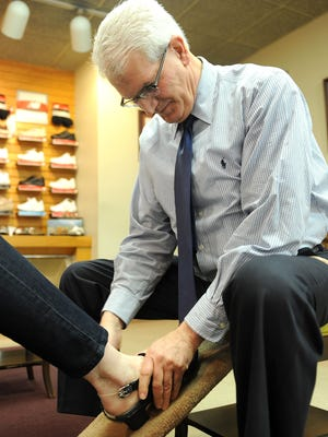 Jeff Delianides fits a shoe on a customer at Crowe's Shoes Wednesday afternoon. Crowe's Shoes has been serving Mansfield for over 73 years.