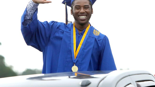A graduate waves as he stands in the back of a truck waiting to walk across the stage during the 2020 Newberry High School graduation ceremony at the Gainesville Raceway Monday. Public schools have been closed due to the COVID-19 pandemic, so Alachua County Public Schools officials set up a socially distant graduation for seniors.