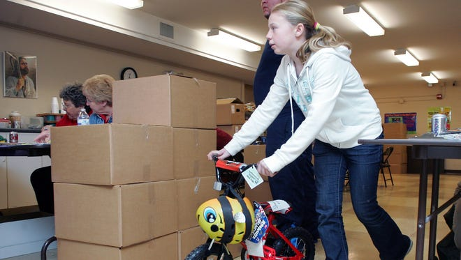 Brianna Sawyers, 11, a volunteer, helps deliver a bicycle to a family in December 2014, during the Christmas Cheer program pickup at the Salvation Army. The Salvation Army is in the process of collecting donations for this Christmas.