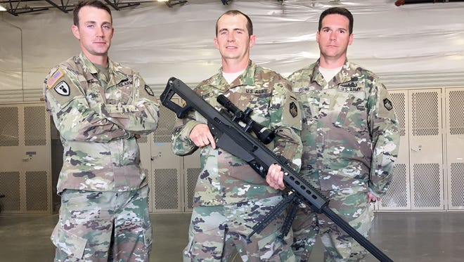 From left, Staff Sgt. Zachary Fife, Capt. Chet Garner and Sgt. Derek Lieding display the M107 Barrett sniper rifle.