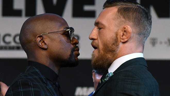 Floyd Mayweather Jr. (L) and UFC lightweight champion Conor McGregor face off during a news conference at the KA Theatre at MGM Grand Hotel & Casino on August 23, 2017 in Las Vegas, Nevada. The two will meet in a super welterweight boxing match at T-Mobile Arena on August 26 in Las Vegas.