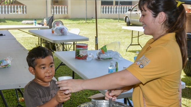 In this file photo, a sanctuary volunteer offers a cup of corn soup to a child at the Guam Homeless Coalition's annual Passport to Services in Hagåtña.