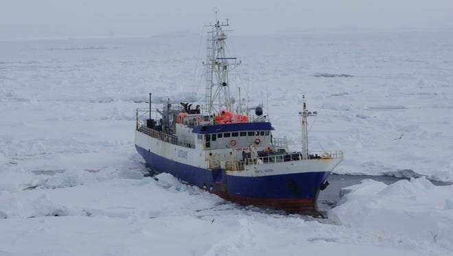 In this image provided by the U.S. Coast Guard, the Australian fishing vessel the Antarctic Chieftain is seen from the the Coast Guard Cutter Polar Star as the cutter begins breaking up the ice around it.