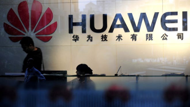 Staff and visitors walk pass the lobby at the telecommunications equipment firm Huawei Technologies in Wuhan, China on October 8, 2012.