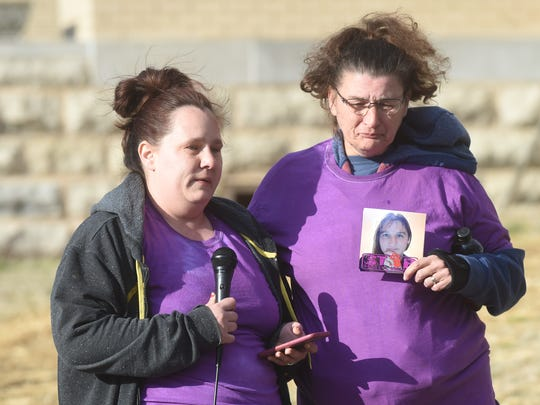 Nicole Brakebill speaks while her mother, Loretta Russell, holds up a picture of her sister Kirstie Headley, who was stabbed to death by her former husband. The women were attending a vigil hosted by the domestic violence shelter Serenity Inc. in honor of Kirstie.