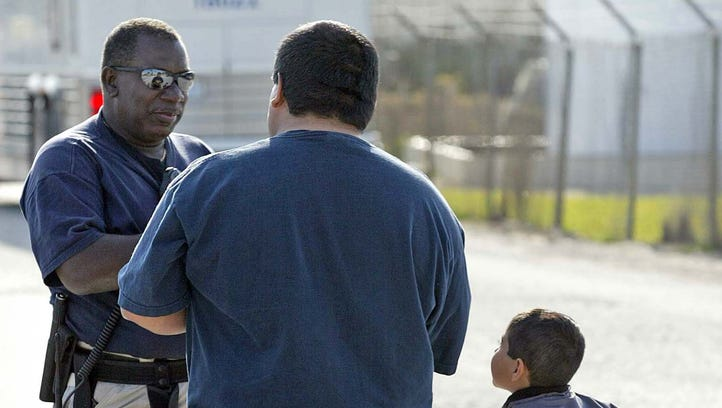 Eli Rodriguez, center, talks with an Immigration and