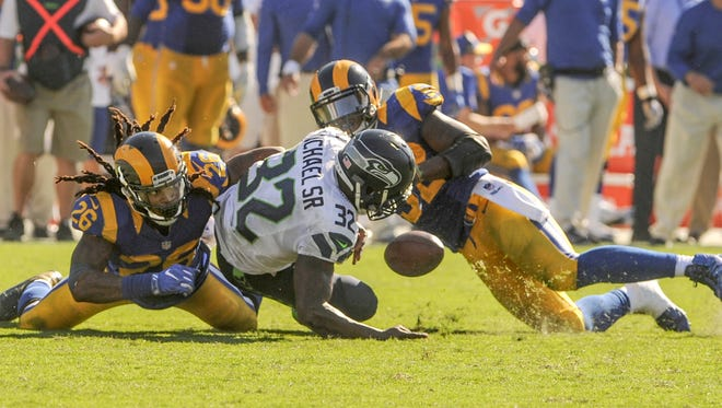 Seahawks running back Christine Michael loses the ball after being hit by the Rams' Mark Barron, left, and Alec Ogletree late in the fourth quarter Sunday. Ogletree recovered the fumble to clinch a 9-3 win in the Rams' first regular-season game since returning to Los Angeles.