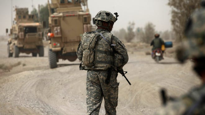 A U.S. Army soldier walks along a road during a day of joint missions with the Afghan Army, in Zhari district, Kandahar province, southern Afghanistan, Aug. 26, 2010.
