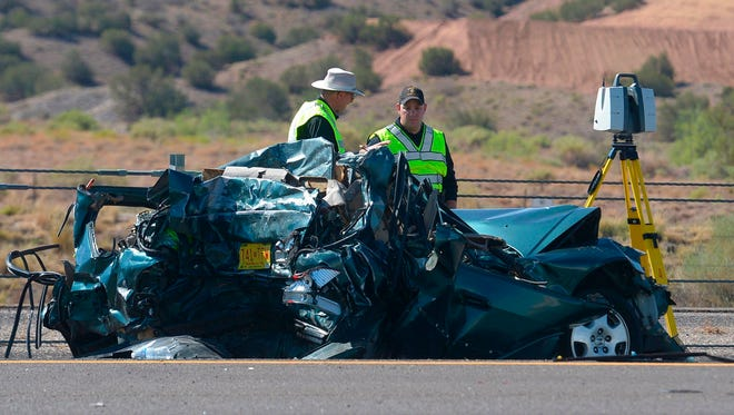 Emergency personnel work at the scene of a deadly multi-vehicle crash involving a bus that occurred on Interstate 25 just north of Bernalillo, on Sunday, July 15, 2018.