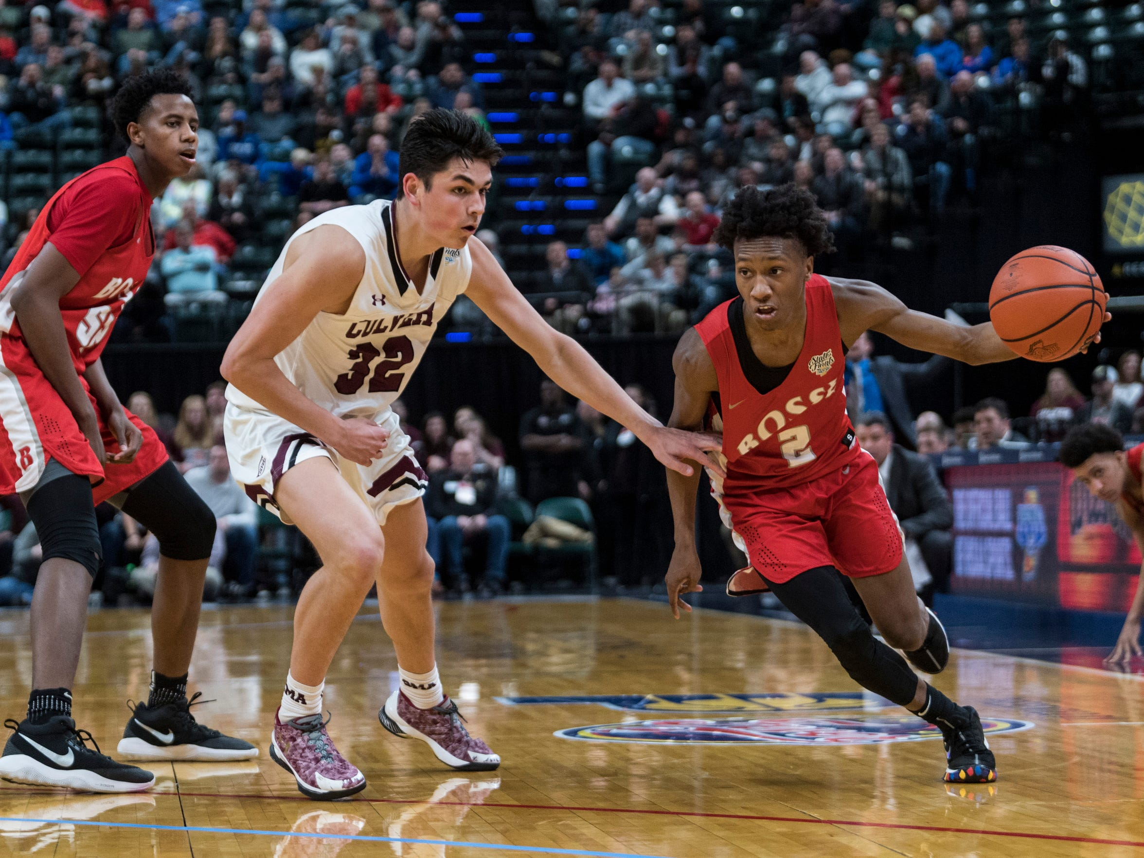 Bosse's Mekhi Lairy (2) drives past Culver Academies defenseman Trey Galloway (32) during the IHSAA Class 3A State Championship at Bankers Life Fieldhouse in Indianapolis, Saturday, March 24. The Bulldogs were defeated by the Culver Academies Eagles, 64-49.