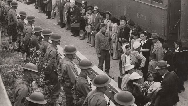 During World War II, the U.S. government forced 120,000 people of Japanese ancestry into prison camps. In this photo, guards watch as Japanese men, women and children wait to board a train that will take them to a prisoner of war camp. Japanese internment camps in New Mexico will be the topic of a panel on  Nov. 17 at the Health and Social Services Auditorium on campus.