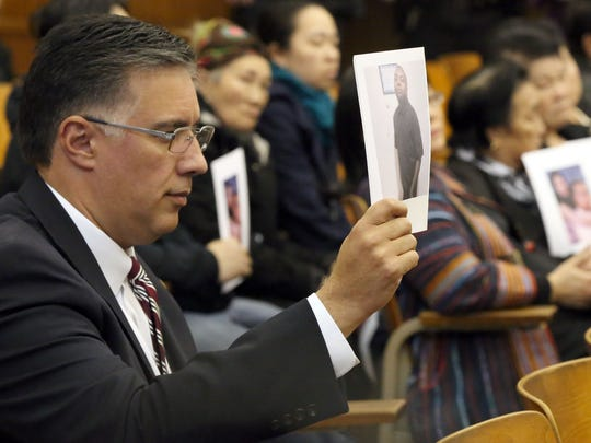Darryl D. Morin, of the League of United Latin American Citizens, holds a photo of Jesus R. Manso-Perez during a court hearing for the man charged with killing him.