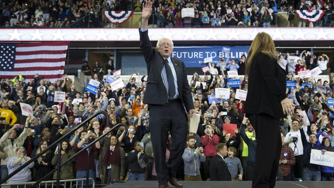 Jane Sanders, right, and her husband Democratic presidential candidate Sen. Bernie Sanders, I-Vt., arrive for a rally at Eastern Michigan University on Monday in Ypsilanti.