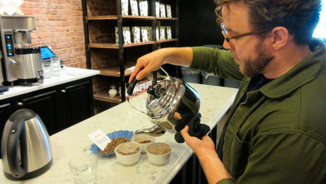 This July 24, 2016 image shows Peter Higgins, tasting room manager at Parlor Coffee, pouring hot water over ground coffee during a coffee tasting, known as a cupping, at the company's Brooklyn, New York, facility.