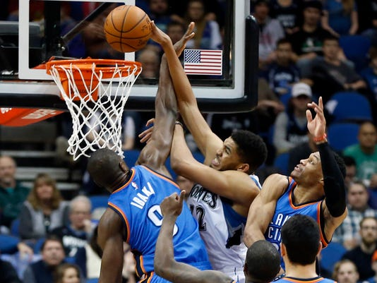 Minnesota Timberwolves' Karl-Anthony Towns, center, manages to score as Oklahoma City Thunder's Serge Ibaka, left, of Republic of Congo, and Russell Westbrook defend in the second half of an NBA basketball game, Wednesday, Jan. 27, 2016, in Minneapolis. The Thunder won 126-123. (AP Photo/Jim Mone)