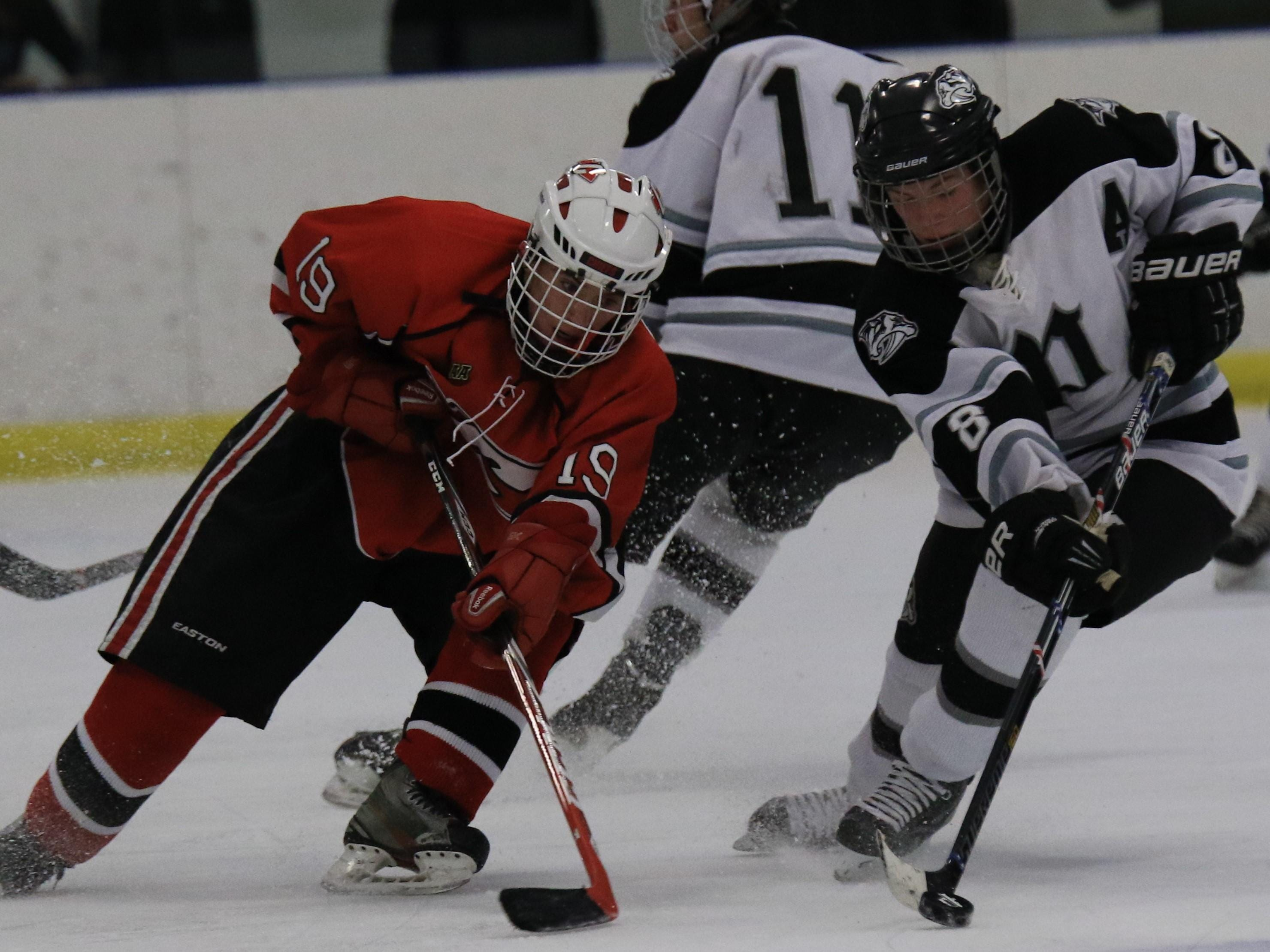 In pursuit of the puck are Canton's Matthew Eastman (No. 19) and Plymouth's Ricky Covault (No. 8).