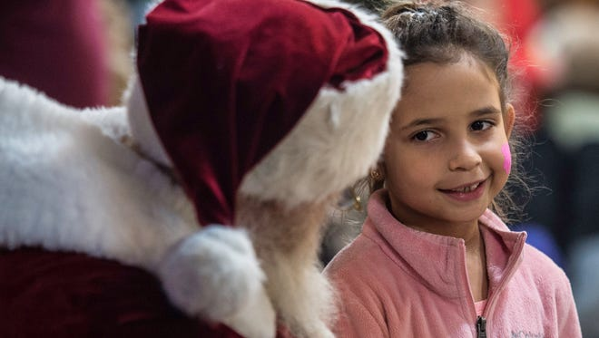 A girl tells Santa Claus what she wants for Christmas during the 13th annual Old Fashioned Christmas Festival in the Depot District, Richmond, on Tuesday, Nov. 28, 2017.