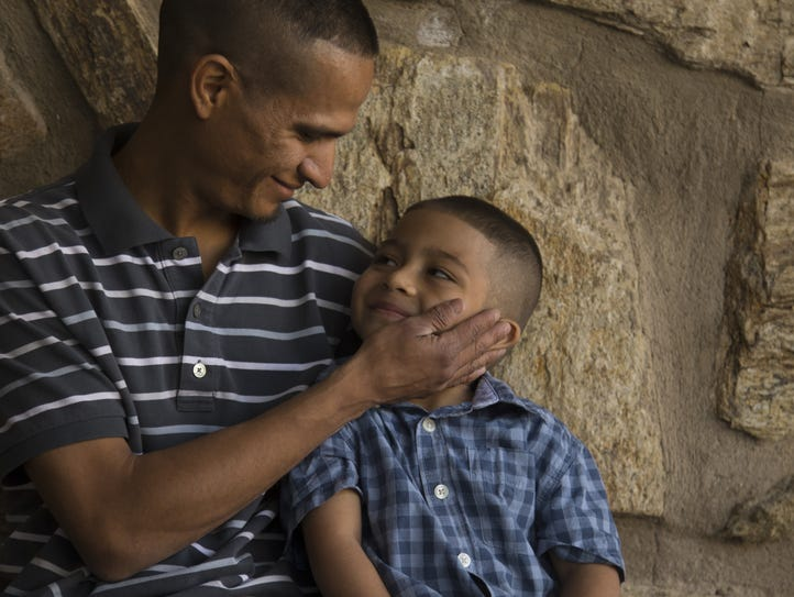 Jesus Berrones holds the cheek of his 5-year-old son