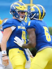Delaware quarterback J.P. Caruso celebrates with receiver Jamie Jarmon after the two connected for a 27-yard touchdown pass in the second quarter of Delaware's 17-0 win at Delaware Stadium Saturday.