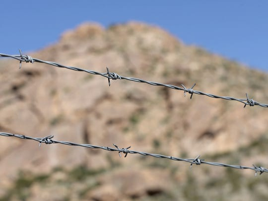 Barbed wire and chain-link fencing separates Castner