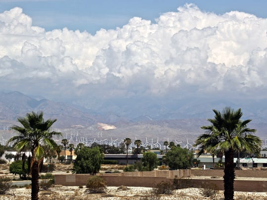 Storm clouds are forming above mountains near the Coachella Valley Sunday. They're expected to drop rain onto the desert through the evening.