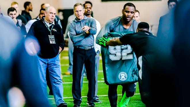 MSU Football Head Coach Mark Dantonio, center, points out a defensive linemen drill to Baltimore Ravens Defensive Coordinator Dean Pees, left, at NFL Pro Day.