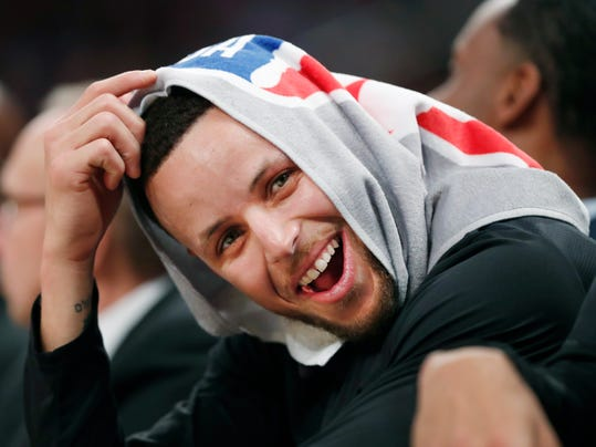 Golden State Warriors guard Stephen Curry, his head covered by a towel, laughs with teammates during the second half of an NBA basketball game against the New York Knicks, Monday, Feb. 26, 2018, in New York. (AP Photo/Kathy Willens)
