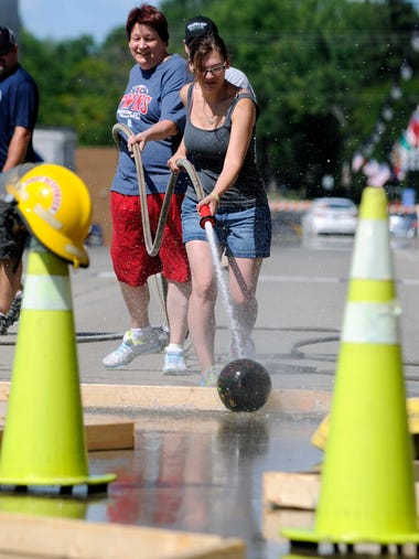 A woman begins her team's water bowling challenge on