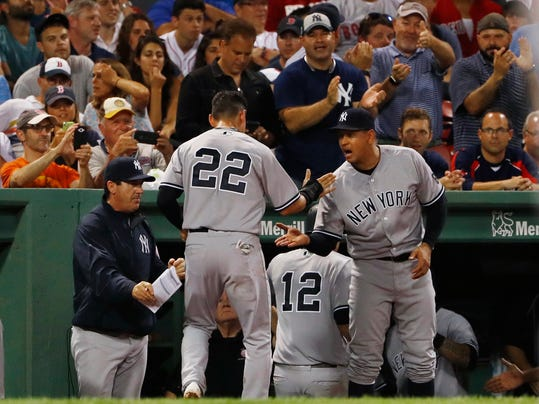 New York Yankees' Jacoby Ellsbury (22) is congratulated by teammate Alex Rodriguez, right, after he and Chase Headley (12) scored on a double by Starlin Castro during the seventh inning of a baseball game against the Boston Red Sox at Fenway Park in Boston on Wednesday, Aug. 10, 2016. (AP Photo/Winslow Townson)