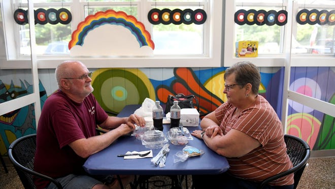 "Randy and Carol Sauers of Louisville eat lunch in the ""Yellow Submarine""-themed Pepperland Porch at Berd-House Deli in Canton Township."