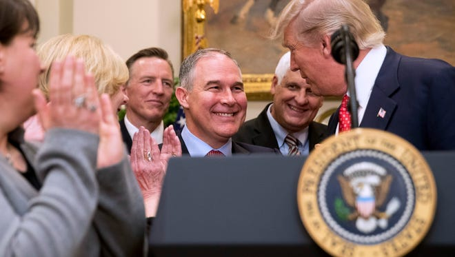 President Donald Trump shakes hands with Environmental Protection Agency Administrator Scott Pruitt (center) Feb. 28 in the Roosevelt Room in the White House in Washington.
