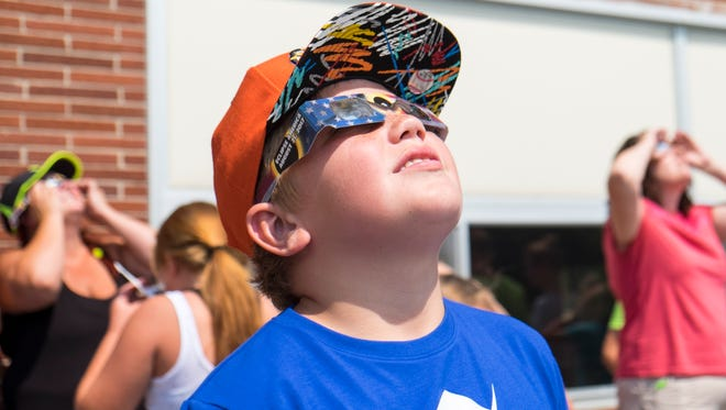 Paul Chenault, 11, looks at the sun during the eclipse on Aug. 21. Fort Gratiot Middle School sixth grade science teacher Gary Kivel organized a day for his incoming students to watch the eclipse and learn about the power of the sun.