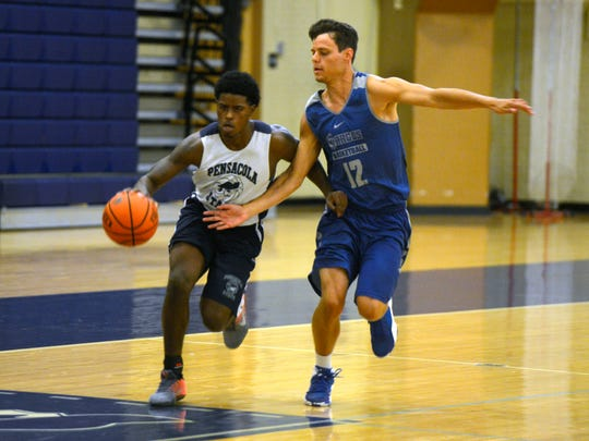 Pensacola State's Cameron Allen and West Florida's Jason Laatsch go down court Sunday during the UWF-PSC scrimmage at PSC.