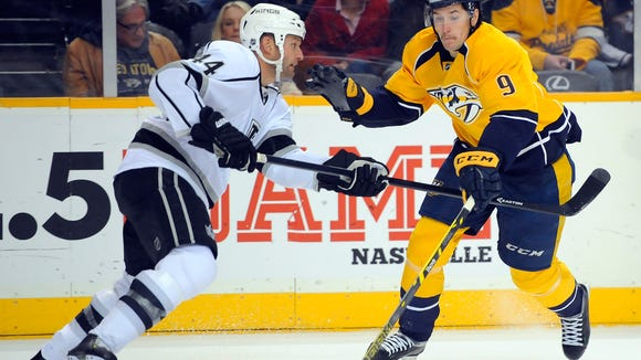 Nov 25, 2014; Nashville, TN, USA; Nashville Predators center Filip Forsberg (9) attempts a move around Los Angeles Kings defenseman Robyn Regehr (44) during the first period at Bridgestone Arena. Mandatory Credit: Christopher Hanewinckel-USA TODAY Sports