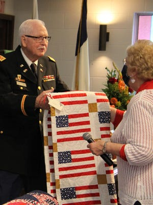 Army veteran Joe Crews receives a patriotic quilt from Donna Leach, leader of the Piecemakers quilt group.