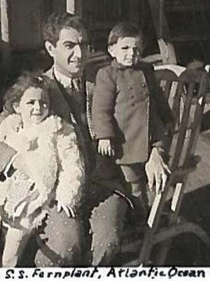 Suzy Kane, then 4 years old, and her little brother Frankie (right) with their father, Nejib Tooni, aboard a Norwegian tanker en route to America in 1944. Kane has written a book about her parents' journey to be together.